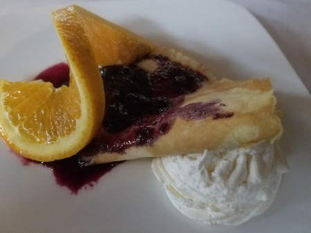 Crepes featuring orange infused ricotta and seasonal berries